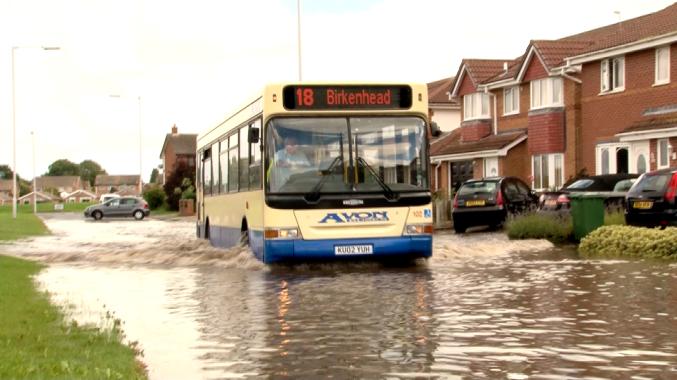 Bus struggles through Moreton flood water on Wednesday
